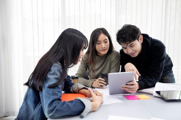 Grupa studentów uśmiechnij się i za pomocą tabletu pomaga także dzielić się pomysłami w pracy i projekcie