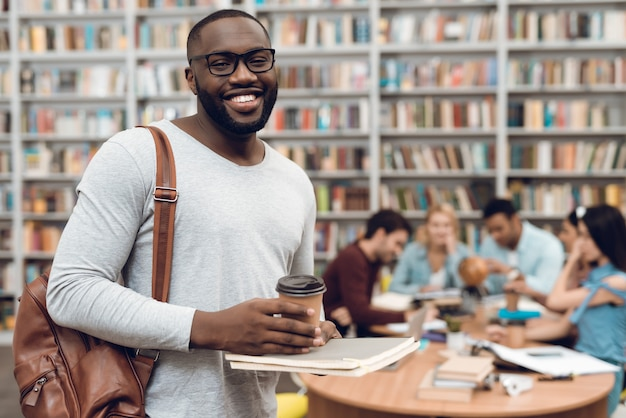Grupa studentów w bibliotece i czarny facet z kawą.