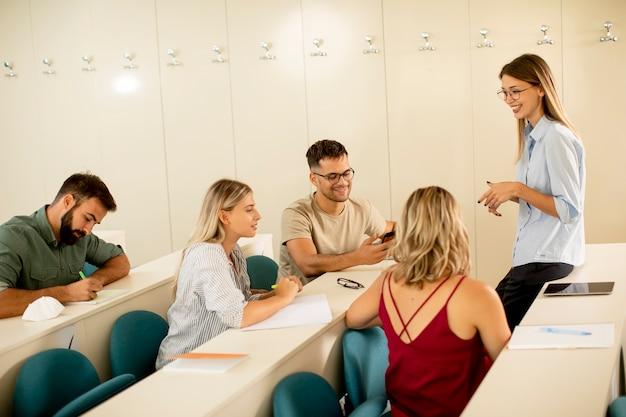 Grupa studentów w klasie z młodą asystentką