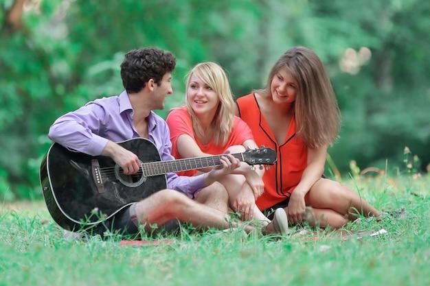 Grupa studentów z gitarą relaksuje się na trawie w parku miejskim.