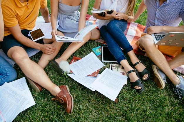 Grupa studentów z książek i tabletu studiują razem na zewnątrz, siedzący na trawie.