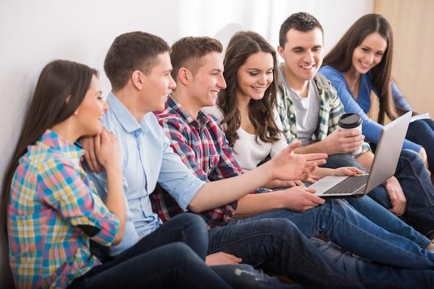 Grupa studentów z laptopem ogląda coś.