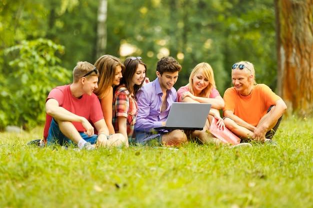 Grupa studentów z laptopem wypoczywa w parku