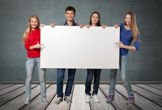 Grupa studentów z pustym znakiem izolowanym na białym tle