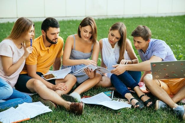 Grupa studiowania ucznie siedzi na trawie z nutowymi książkami
