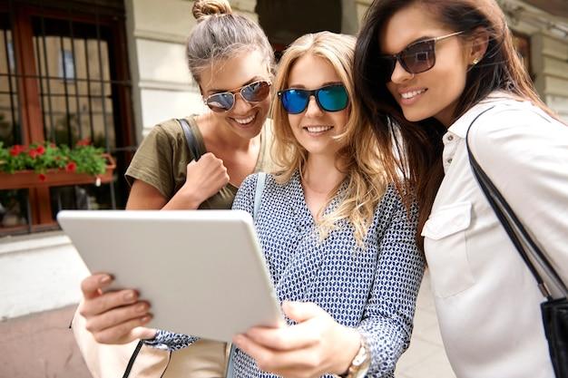 Grupa stylowych kobiet korzystających z miasta i za pomocą cyfrowego tabletu