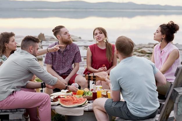 Grupa stylowych młodych ludzi spędzających czas nad pięknym jeziorem, siedząc przy stole, jedząc letnie owoce, rozmawiając i ciesząc się razem wieczorem