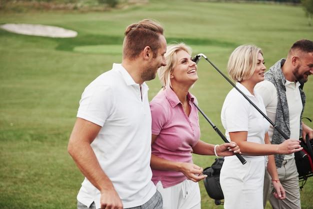 Grupa stylowych przyjaciół na polu golfowym uczy się grać w nową grę. drużyna odpocznie po meczu