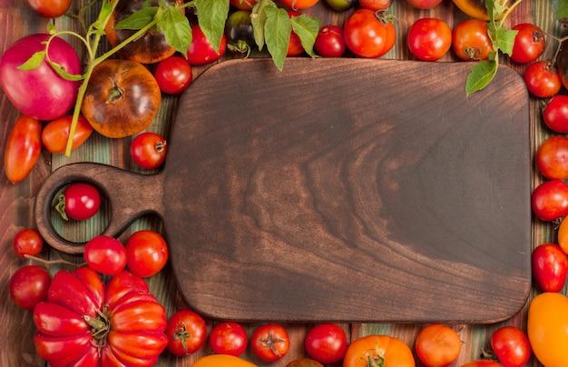 Grupa świeżych pomidorów i drewnianą deską do krojenia