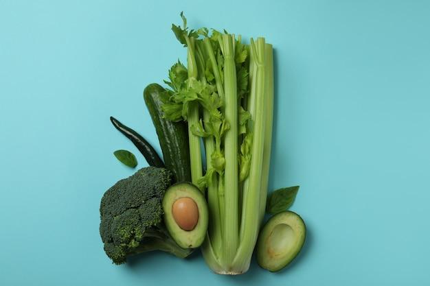 Grupa świeżych zielonych warzyw na niebieskim tle