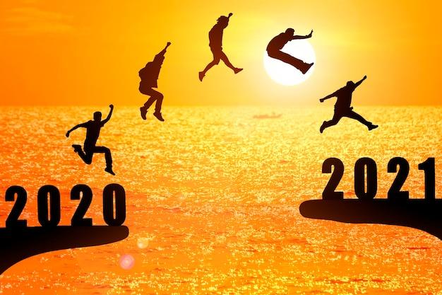 Grupa sylwetka młodych mężczyzn skaczących między 2020 a 2021 rokiem z pięknym zachodem słońca nad morzem.