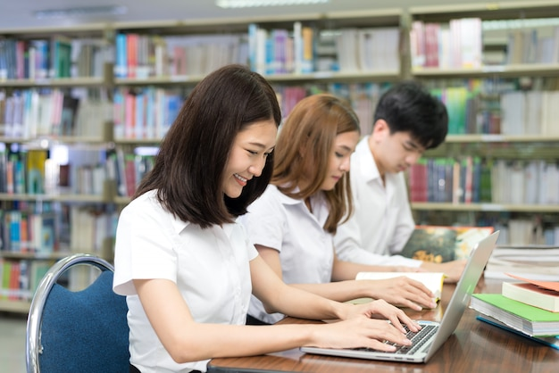 Grupa szczęśliwi azjatyccy ucznie z laptopem