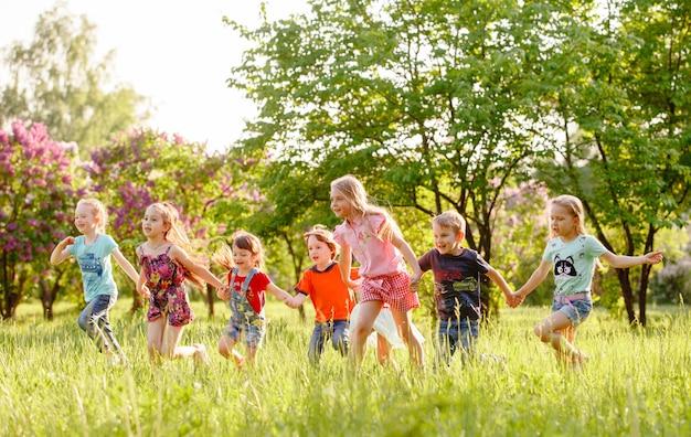 Grupa szczęśliwi dzieci chłopiec i dziewczyny biegamy w parku na trawie na pogodnym letnim dniu