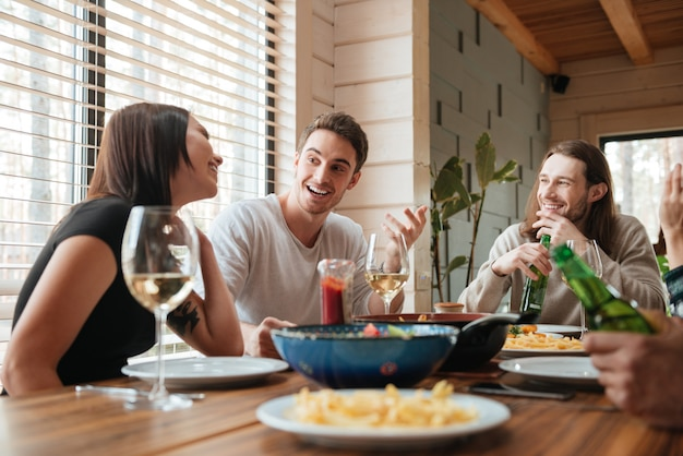 Grupa szczęśliwi ludzie je i opowiada przy stołem