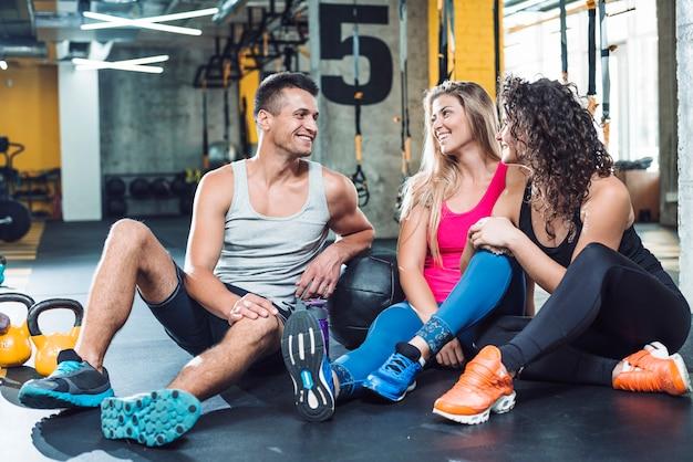 Grupa szczęśliwi ludzie siedzi wpólnie po treningu