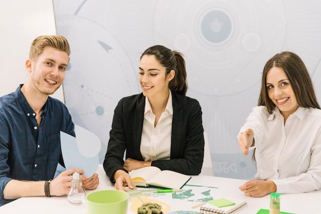 Grupa szczęśliwi męscy i żeńscy biznesmeni siedzi w biurze