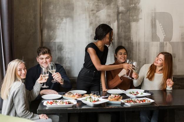 Grupa szczęśliwi młodzi ludzie cieszy się gościa restauracji
