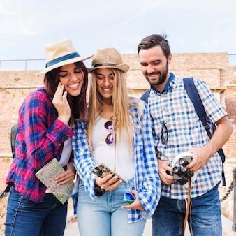 Grupa szczęśliwi przyjaciele patrzeje telefon komórkowego