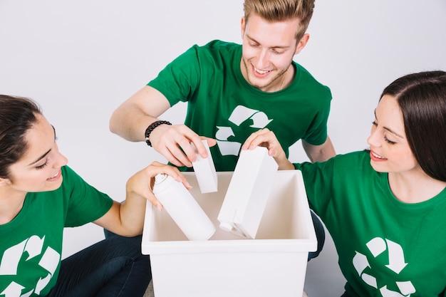 Grupa szczęśliwi przyjaciele rzuca butelki w białym kosz na śmiecie