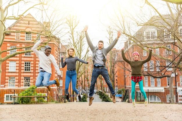 Grupa szczęśliwi przyjaciele skacze wpólnie przy parkiem