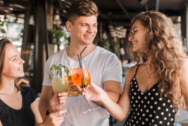 Grupa szczęśliwi przyjaciele wznosi toast napoje