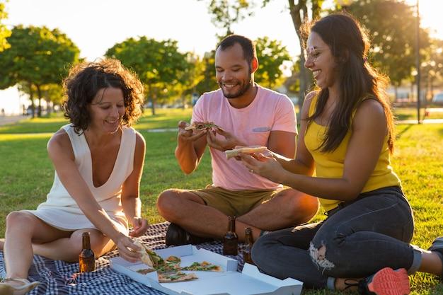 Grupa szczęśliwi zamknięci przyjaciele je pizzę w parku