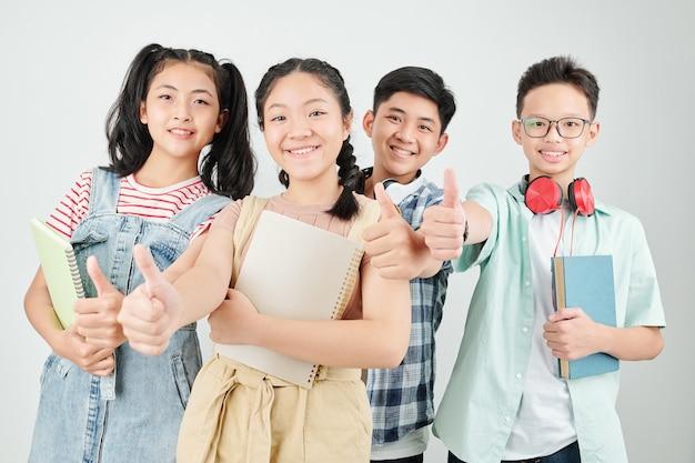 Grupa szczęśliwych azjatyckich dzieci w wieku szkolnym z książkami i zeszytami pokazuje kciuk do góry