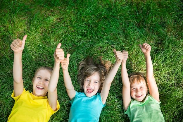 Grupa szczęśliwych dzieci bawiących się na świeżym powietrzu dzieci bawiące się w wiosennym parku przyjaciele leżący na trawie