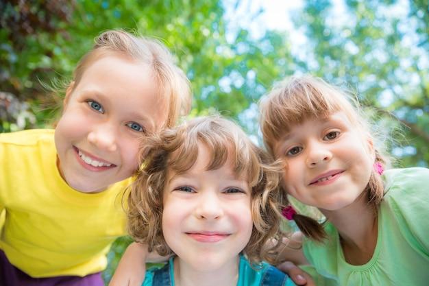Grupa szczęśliwych dzieci bawiących się na świeżym powietrzu dzieci bawiące się w wiosennym parku