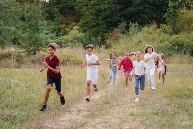 Grupa szczęśliwych dzieci biegnie i bawi się w parku podczas zachodu słońca