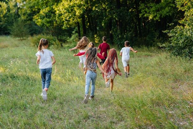 Grupa szczęśliwych dzieci biegnie i bawi się w parku podczas zachodu słońca.