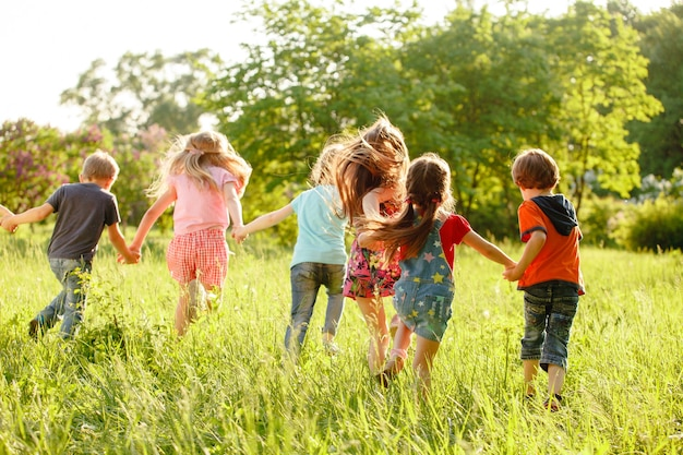 Grupa szczęśliwych dzieci chłopców i dziewcząt biegających w parku na trawie w słoneczny letni dzień.