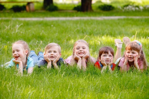 Grupa szczęśliwych dzieci chłopców i dziewcząt biegnie w parku po trawie w słoneczny letni dzień.