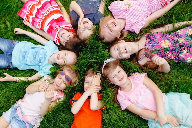 Grupa szczęśliwych dzieci chłopców i dziewcząt ustanawiające w parku na trawie w słoneczny letni dzień.