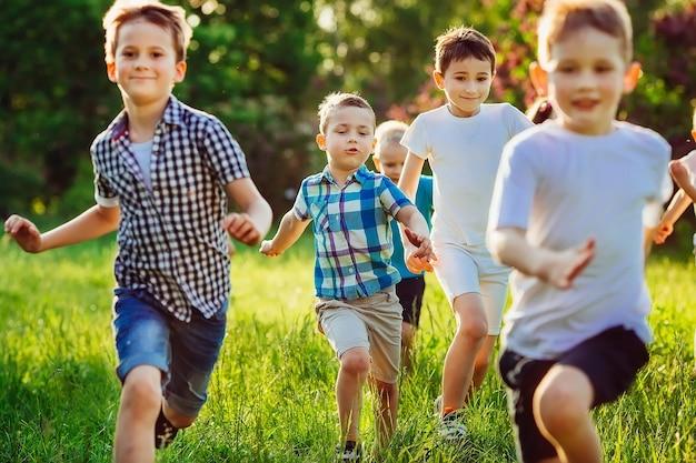 Grupa szczęśliwych dzieci chłopców i dziewczynek biega po parku po trawie w słoneczny letni dzień.