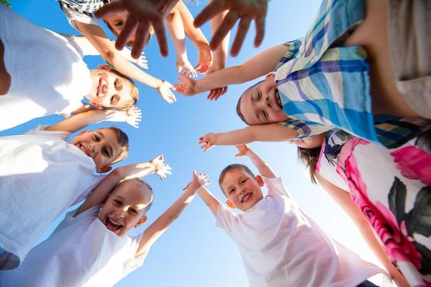 Grupa szczęśliwych dzieci chłopców i dziewczynek w parku z widokiem z ziemi