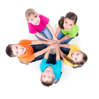 Grupa szczęśliwych dzieci siedzi na podłodze w kręgu, trzymając się za ręce i patrząc w górę - na białym tle.