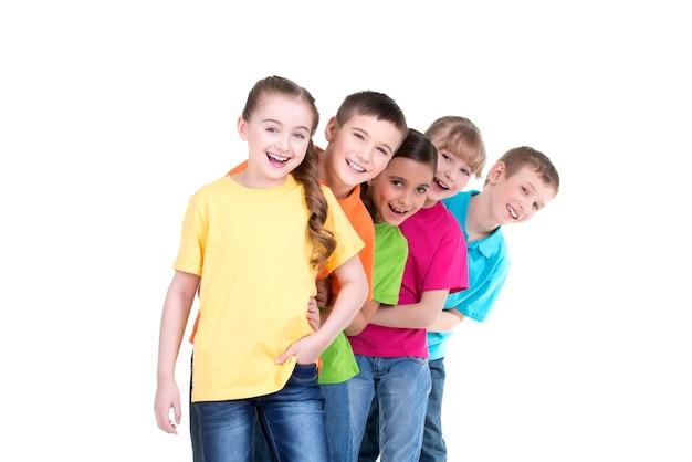 Grupa szczęśliwych dzieci w kolorowych koszulkach stoją za sobą na białym tle.