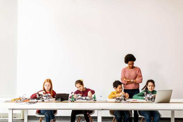 Grupa szczęśliwych dzieci z ich african american nauczycielką
