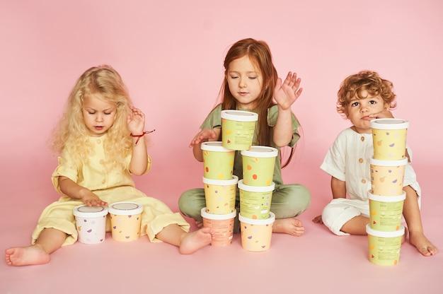 Grupa szczęśliwych dzieciaków bawiących się papierowymi pudełkami. opakowania ekologiczne i jednorazowa zastawa stołowa. pomysł na opakowanie.