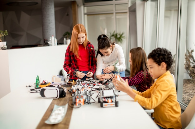Grupa szczęśliwych dzieciaków programujących zabawki elektryczne i roboty w klasie robotyki