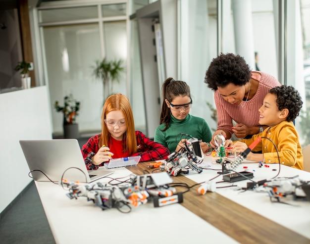 Grupa szczęśliwych dzieciaków z afrykańsko-amerykańską nauczycielką przedmiotów ścisłych z programowaniem laptopów elektrycznych zabawek i robotów w klasie robotyki