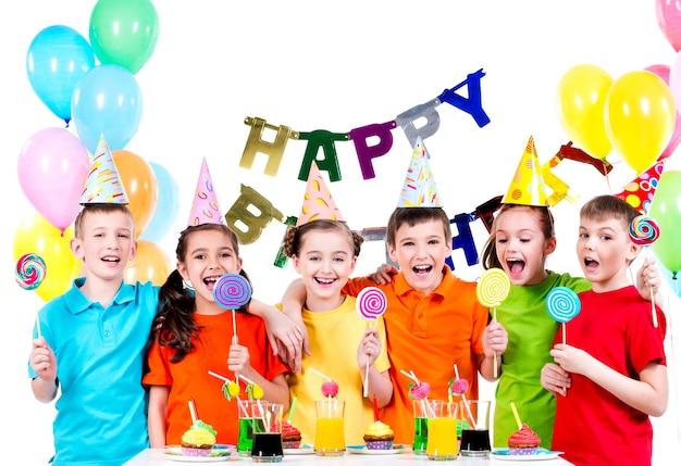 Grupa szczęśliwych dzieciaków z kolorowych cukierków, zabawy na przyjęciu urodzinowym - na białym tle