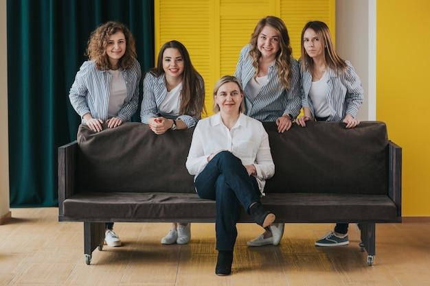 Grupa szczęśliwych dziewcząt pozuje na kanapie
