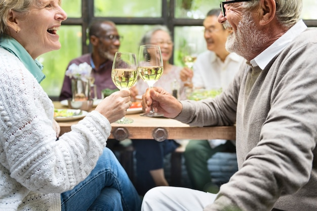 Grupa szczęśliwych emerytowanych seniorów spotykają się w restauracji