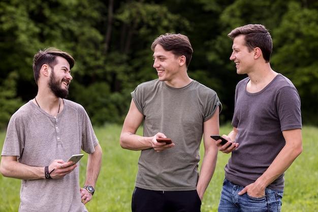 Grupa szczęśliwych facetów ze smartfonami rozmawiających w przyrodzie