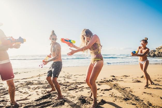 Grupa szczęśliwych i radosnych młodych ludzi bawiących się razem w przyjaźń z bitwą na pistolety wodne na plaży podczas letnich wakacji