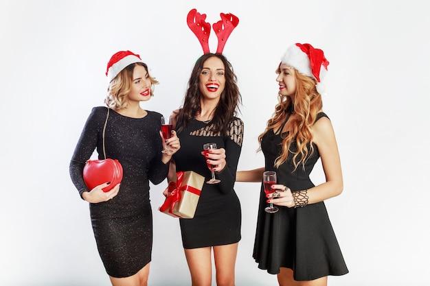Grupa szczęśliwych kobiet uroczystości w słodkie czapki z maskaradą nowego roku spędzają razem wspaniały czas. picie alkoholu, taniec, zabawa na białym tle.