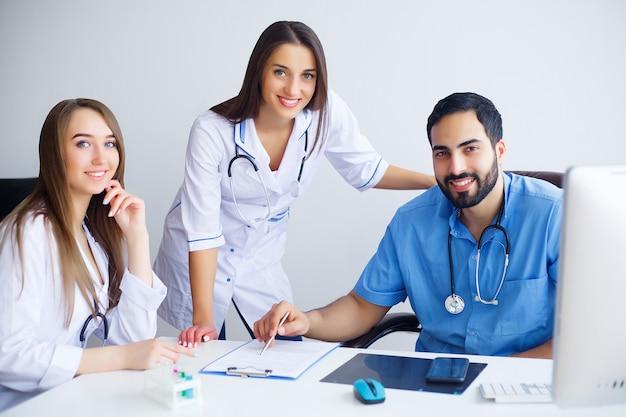 Grupa szczęśliwych lekarzy wielorasowe pracujących razem w klinice
