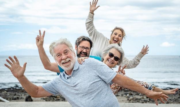 Grupa szczęśliwych ludzi bawiących się razem na morzu, zachmurzone niebo. rodzina wielopokoleniowa gestykulująca pozytywnością i wolnością